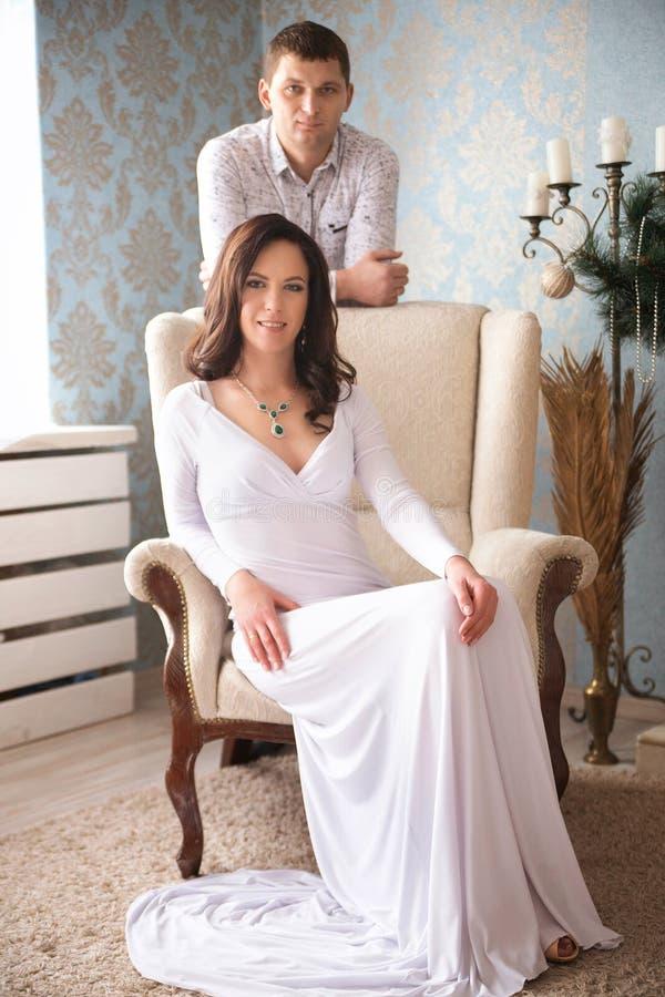 Porträt eines jungen Paares in den eleganten Abendkleidern, die an sitzen lizenzfreie stockfotos
