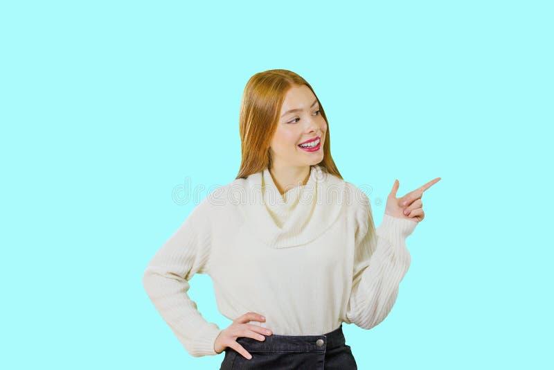 Porträt eines jungen rothaarigen Mädchens, dessen der Seite und dem Lächeln ihren Zeigefinger beim Schauen in Richtung zeigt lizenzfreie stockbilder