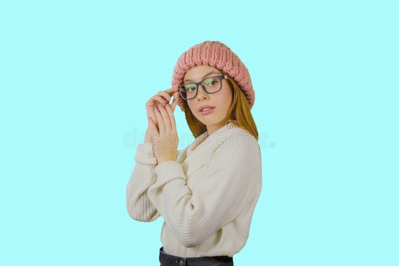 Porträt eines jungen rothaarigen Mädchens in einem gestrickten rosa Hut, der ein Paar Gläser mit einem ernsten Blick hält, ist lizenzfreie stockfotos