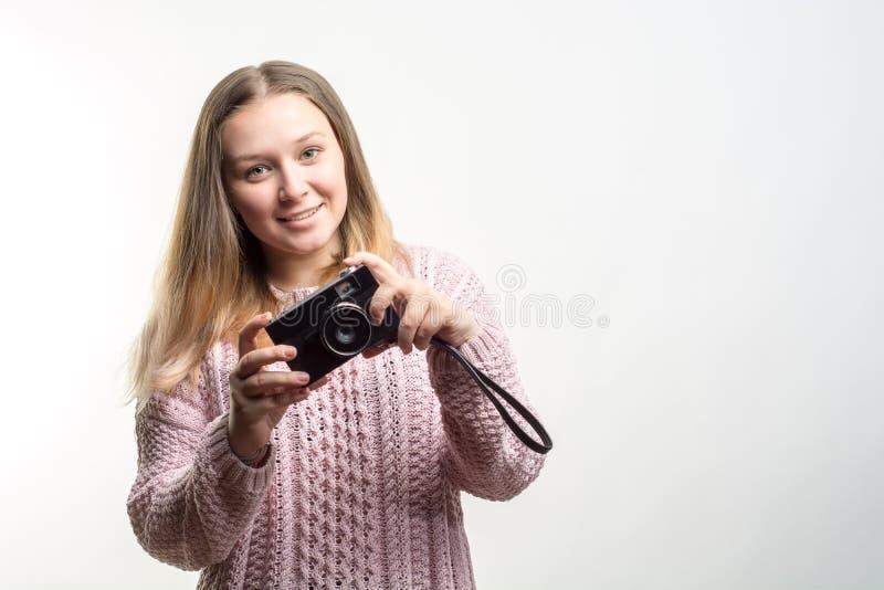 Porträt eines jungen schönen lächelnden blonden Mädchentragens blaß - zacken Sie gestrickte Strickjacke mit einer Weinlesekamera  stockfotografie