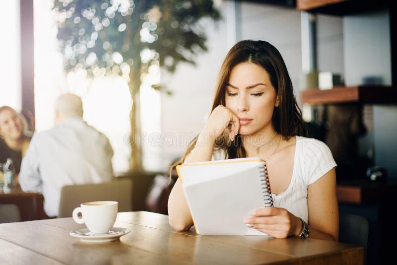 Porträt eines jungen, schönen Mädchens, das in einem Café, ein Papier lesend sitzt stockbild
