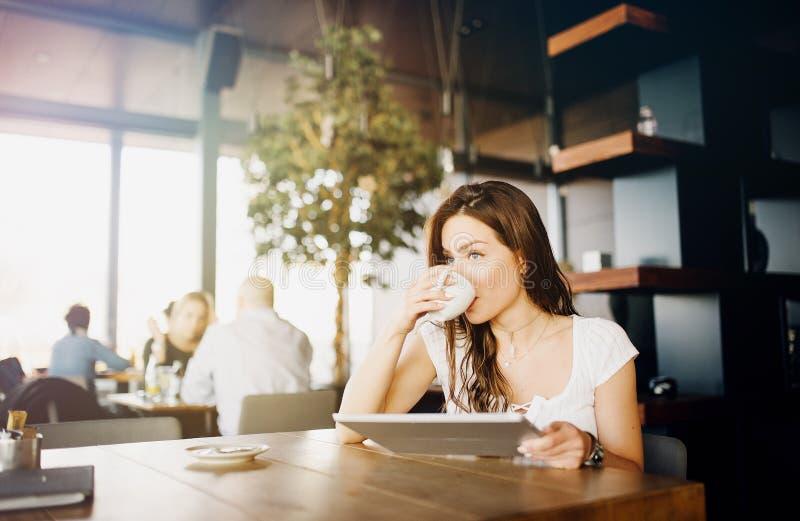 Porträt eines jungen, schönen Mädchens, das in einer Cafeteria, trinkender Kaffee sitzt stockfotografie
