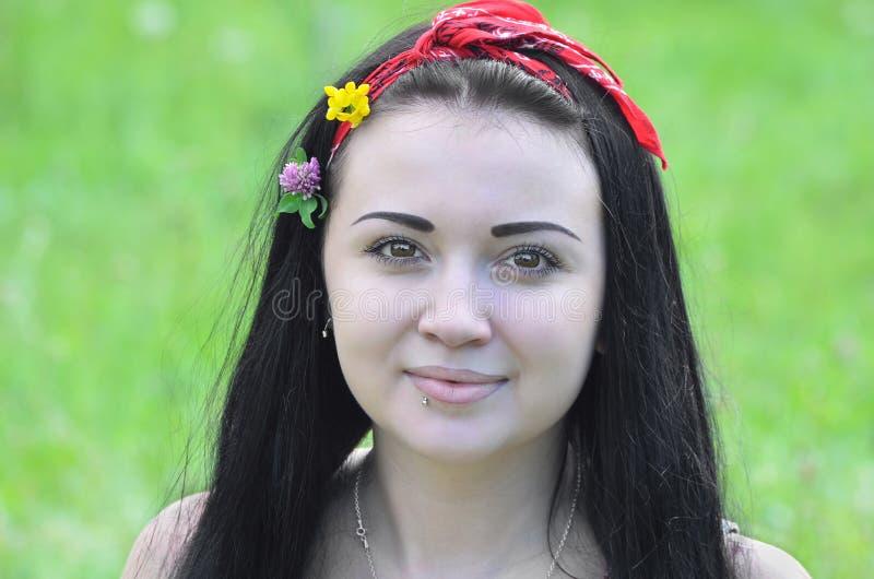 Porträt eines jungen, schönen Mädchens, des Brunette mit Blumen in ihrem Haar und des Schals stockfotografie
