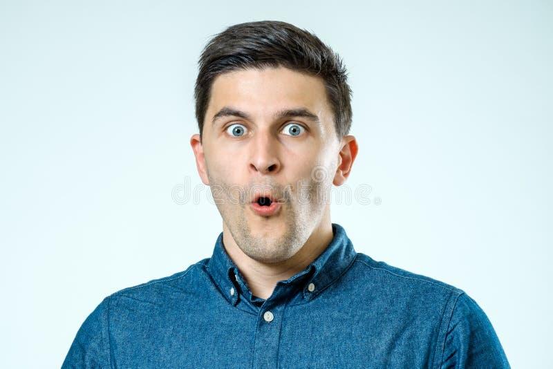 Porträt eines jungen schönen Mannes mit überraschtem Gesichtsausdruck stockfotografie