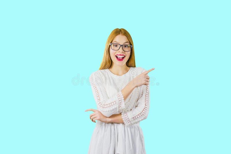 Porträt eines jungen schönen rothaarigen Mädchens in den Gläsern, das emotional mit seinem breiten offenen und Punkten des Munds  lizenzfreies stockfoto