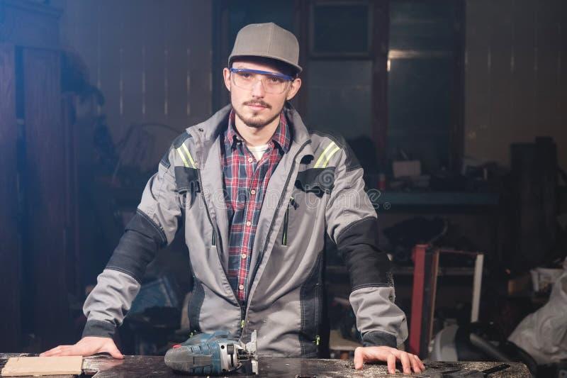 Porträt eines jungen Tischlerschreiners im Overall, der eine Kappe und Schutzbrillen mit einer elektrischen Laubsäge auf Tabelle  lizenzfreies stockbild