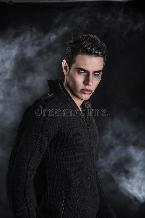 Porträt eines jungen Vampirs-Mannes mit schwarzer Strickjacke lizenzfreies stockfoto