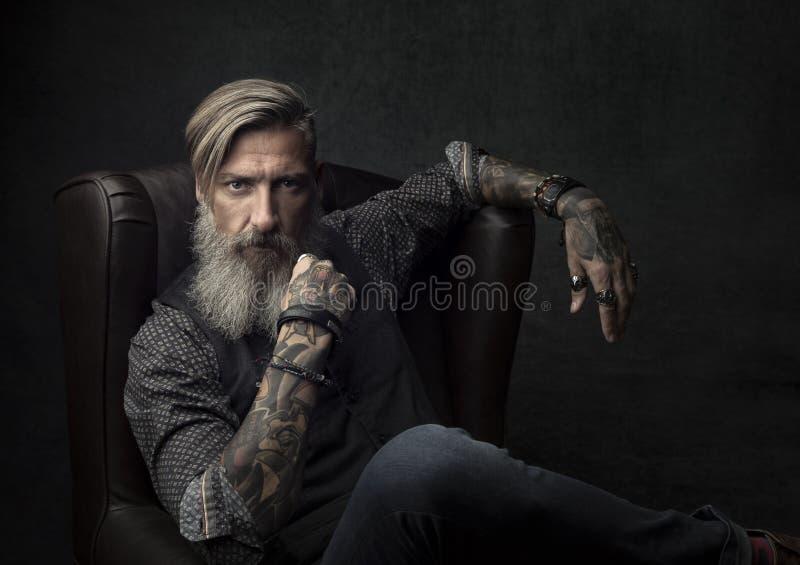 Porträt eines kühlen bärtigen Geschäftsmannes, der auf einem Lehnsessel sitzt stockfotos