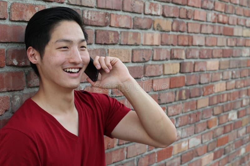 Porträt eines kühlen Kerls, der auf dem Bürgersteig nennt durch Handy sitzt stockbild