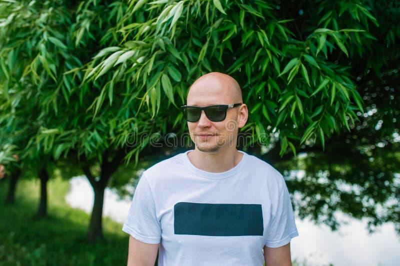Porträt eines kahlen Mannes im Stadtpark stockfotografie