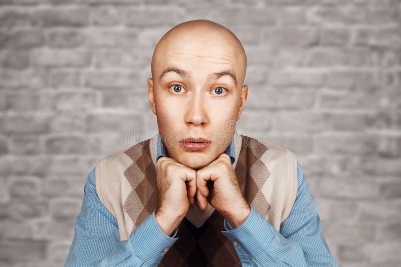 Porträt eines kahlen Mannes mit einer Hand in einem blauen Hemd auf einem weißen Backsteinmauerhintergrund lizenzfreies stockfoto