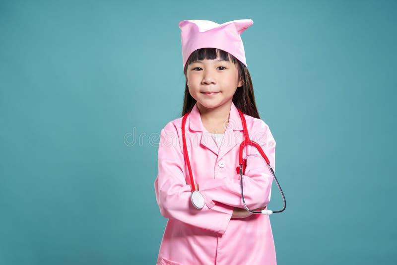 Porträt eines kleinen asiatischen Mädchens in Doktoren einheitlich stockfotografie