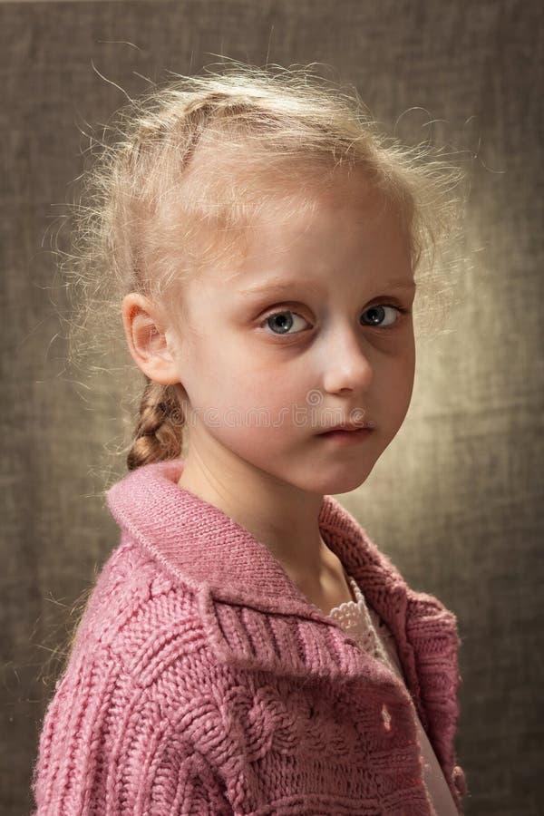 Porträt eines kleinen hellen traurigen Mädchens auf einem hellen Hintergrund stockbilder