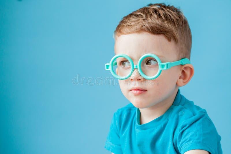 Portr?t eines kleinen Jungen in den Spielzeuggl?sern auf blauem Hintergrund lizenzfreies stockfoto