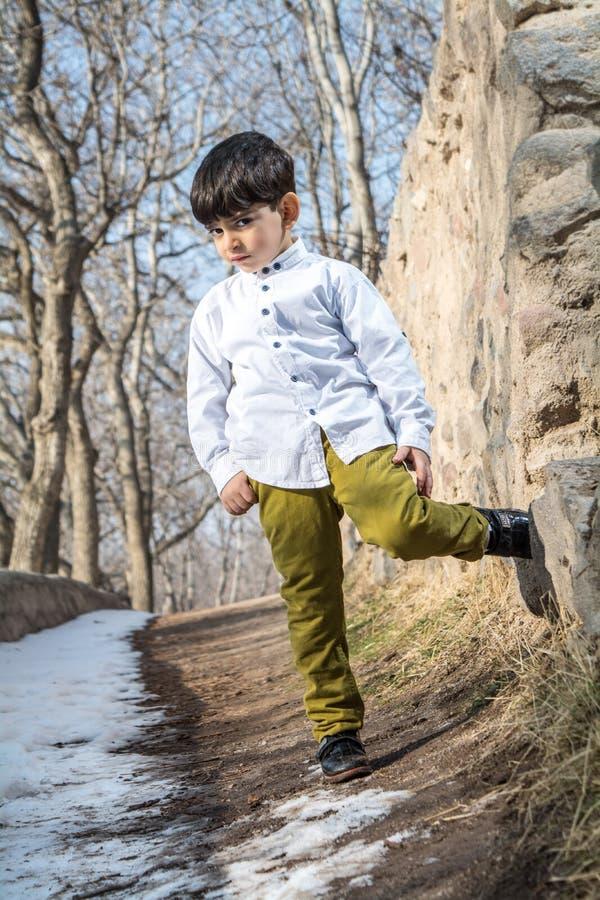 Porträt eines kleinen Jungen der Mode im Garten lizenzfreies stockbild