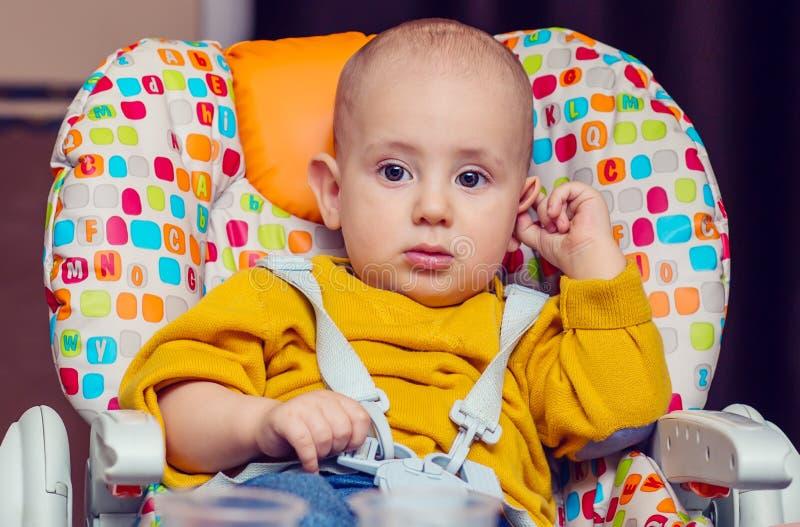 Porträt eines kleinen Jungen in einem Highchair stockfoto