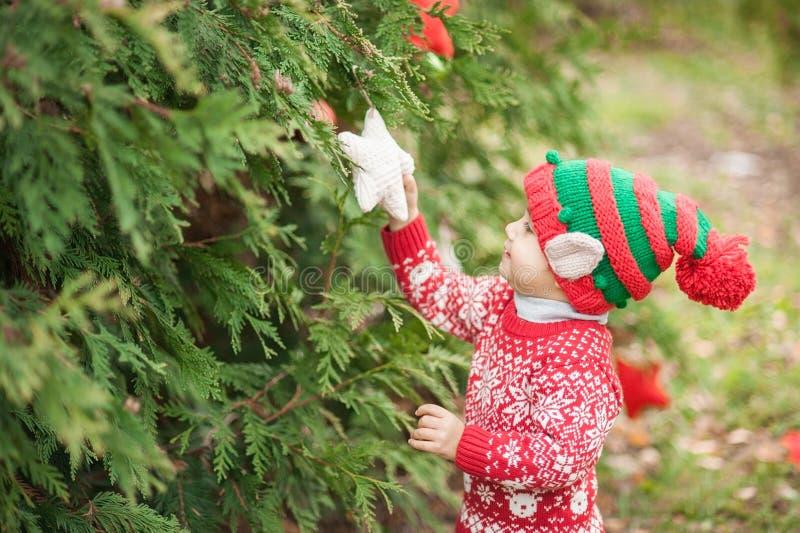Porträt eines kleinen Jungen im Elfenhut und in der roten Strickjacke nahe dem Weihnachtsbaum und der halten Dekoration stockfoto