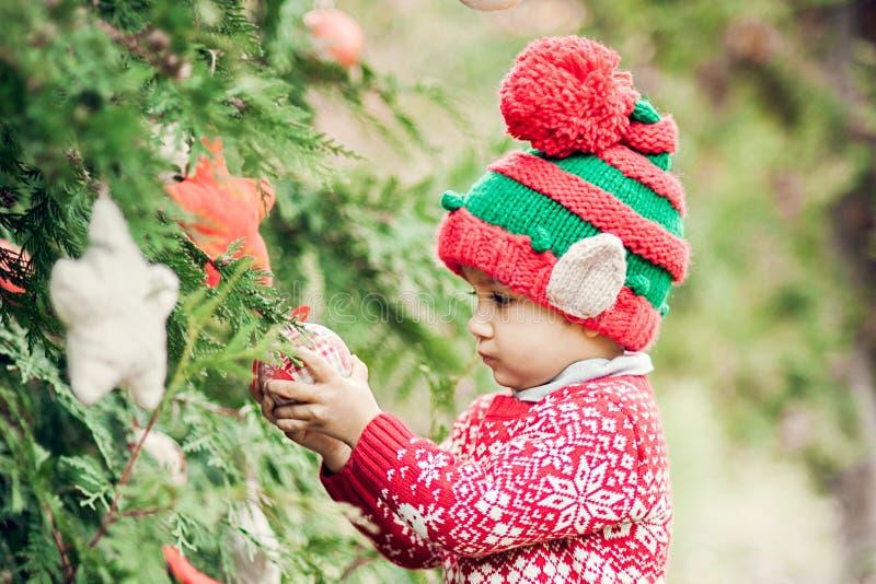 Porträt eines kleinen Jungen im Elfenhut und in der roten Strickjacke nahe dem Weihnachtsbaum und der halten Dekoration lizenzfreies stockfoto