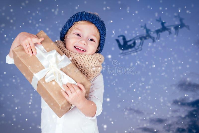 Porträt eines kleinen Jungen mit Geschenk in einem Strickhut auf dunkelblauem Hintergrund Cute blond child mit xmas präsentiert G stockfoto