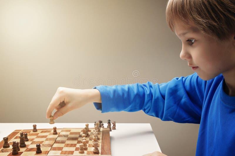Porträt eines kleinen kaukasischen Jungen, der Schach spielt lizenzfreies stockbild