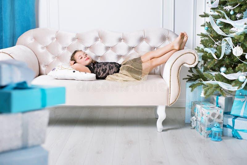 Porträt eines kleinen Mädchens, das auf einem modernen Sofa sich entspannt lizenzfreies stockfoto