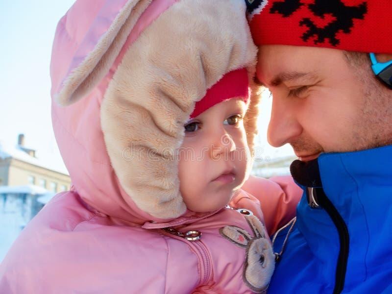 Porträt eines kleinen Mädchens, das Mann auf der Backe küsst lizenzfreies stockbild