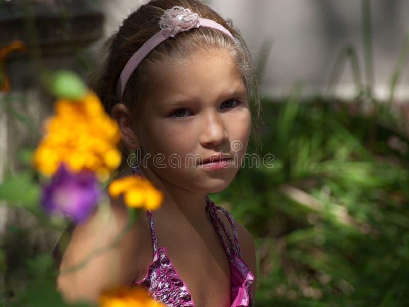 Porträt eines kleinen Mädchens, das wegen der gelben und lila Blumen schaut stockfotografie