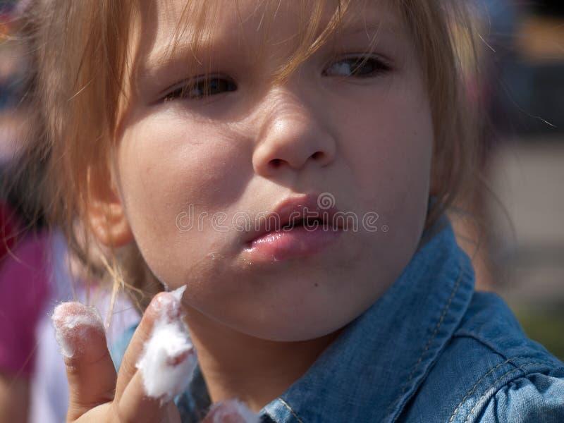 Porträt eines kleinen Mädchens, das Zuckerwatte isst stockbild