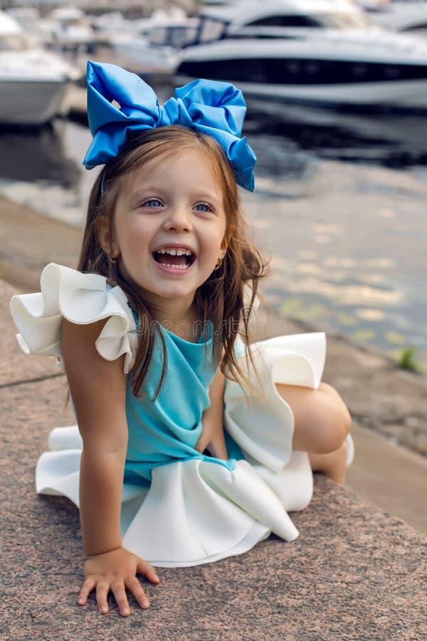 Porträt eines kleinen Mädchens drei Jahre mit dem blauen Bogen auf ihrem Kopf, der lächelt stockfotos