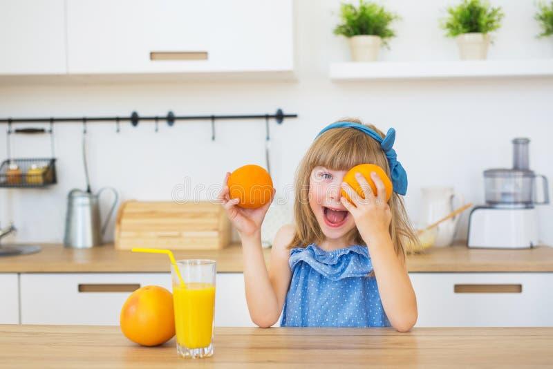Porträt eines kleinen Mädchens in einem blauen Kleid spielt mit Orangen auf einer Tabelle lizenzfreie stockfotos
