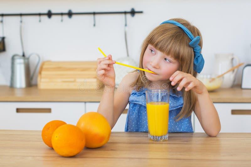 Porträt eines kleinen Mädchens in einem blauen Kleid trinkt einen Orangensaft und denkt lizenzfreie stockfotografie
