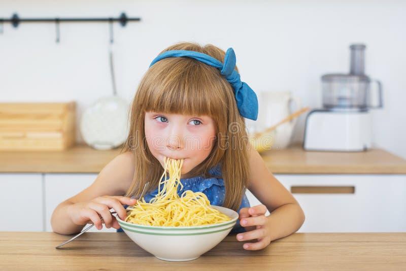 Porträt eines kleinen Mädchens in einem blauen lustigen Kleid isst Spaghettis von einem Teller stockbilder