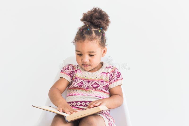 Porträt eines kleinen Mädchens in einem bunten Kleid ein Buch auf einem weißen Hintergrund lesend lizenzfreies stockfoto