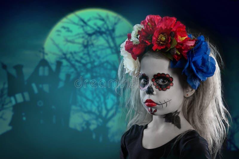 Porträt eines kleinen Mädchens in einem Make-up auf einem Halloween-Kranz mit roten Blumen auf ihrem Kopf stockbilder