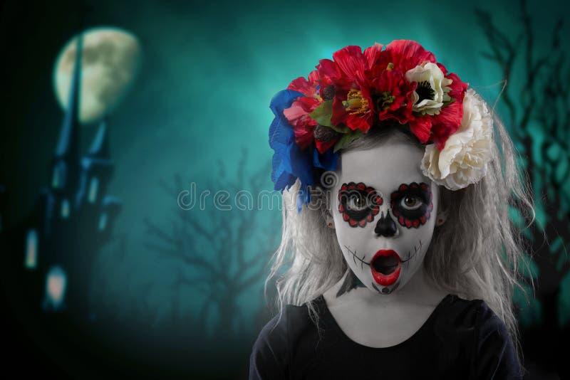 Porträt eines kleinen Mädchens in einem Make-up auf einem Halloween-Kranz mit roten Blumen auf ihrem Kopf stockfoto