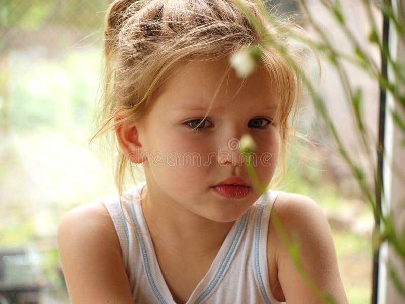 Porträt eines kleinen Mädchens in einem weißen T-Shirt, das heraus von hinten die Stiele von Gänseblümchen an einem Sommertag sch stockbild