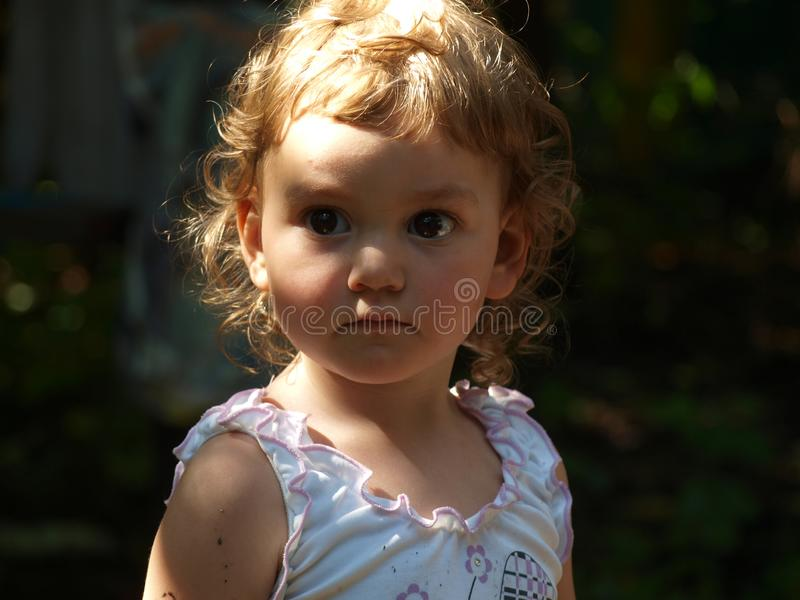 Porträt eines kleinen Mädchens mit dem gelockten Haar und großen den Augen, die ernsthaft den Abstand untersuchen lizenzfreie stockfotos