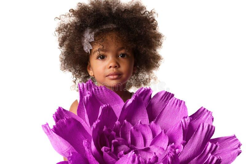 Porträt eines kleinen netten Mädchens mit großem purpurrotem Blumenorigami, lokalisiert stockbilder