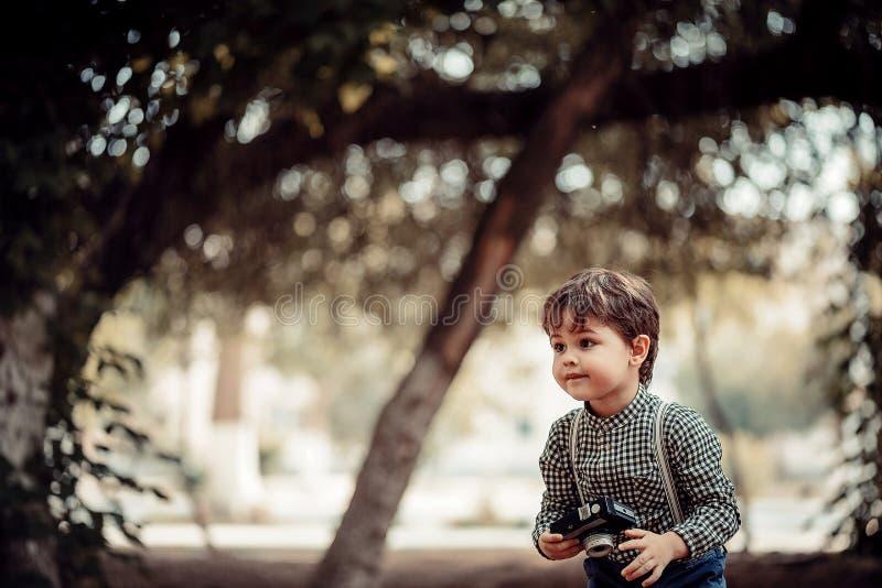 Porträt eines kleinen und sehr netten Jungen kleidete im Retrostil an und saß auf einem Weinlesekoffer auf einem verlassenen Bahn lizenzfreie stockbilder