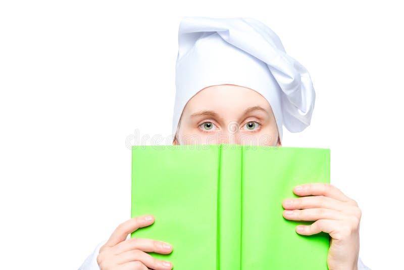 Porträt eines Kochs in einer Kappennahaufnahme, Gesicht bedeckt mit einem Buch des Rezeptkonzeptfotos lokalisiert auf Weiß lizenzfreie stockfotos