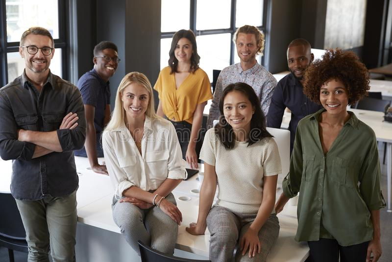 Porträt eines kreativen Geschäftsteams, das auf einem Schreibtisch, lächelnd zur Kamera im Büro, erhöhte Ansicht sich lehnt lizenzfreies stockfoto