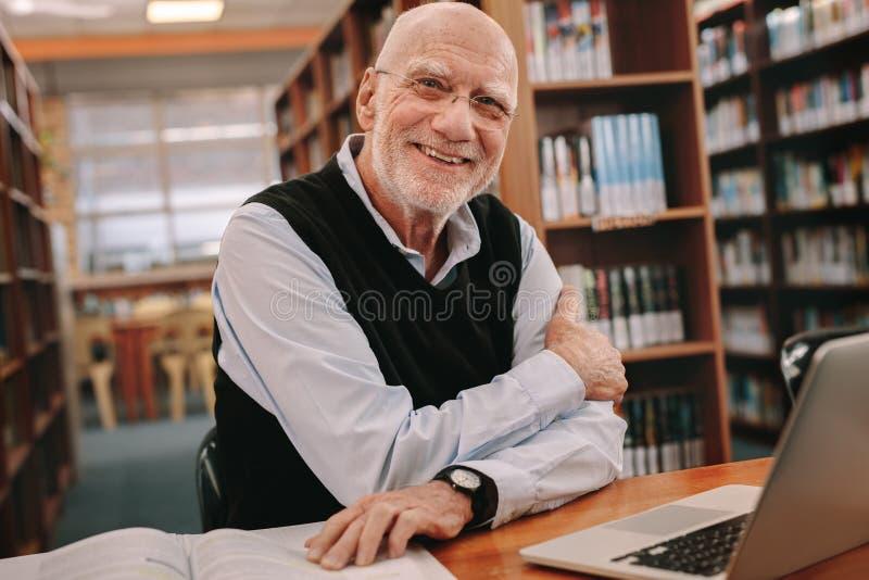 Porträt eines lächelnden älteren Mannes, der in einer Bibliothek sitzt stockfotografie