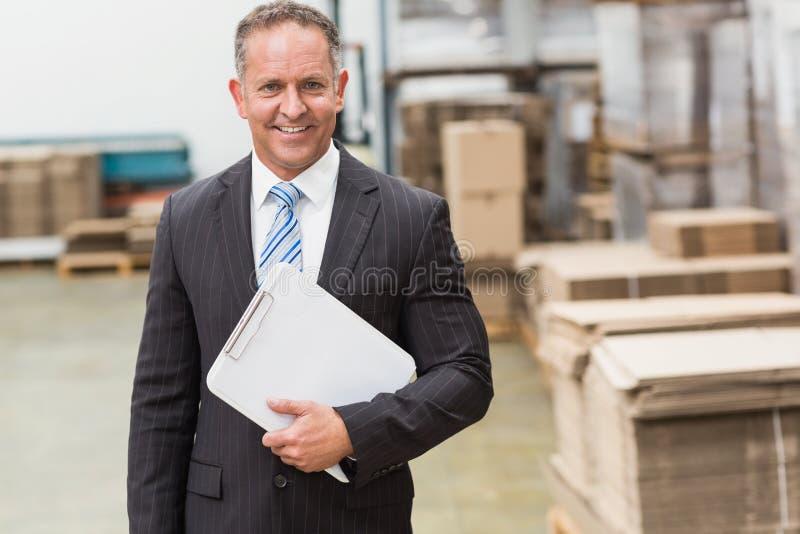 Porträt eines lächelnden Chefs, der Klemmbrett hält lizenzfreie stockfotos