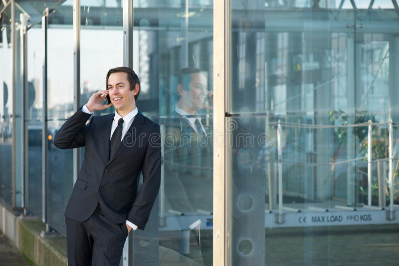 Porträt eines lächelnden Geschäftsmannes, der durch Handy nennt lizenzfreie stockfotografie