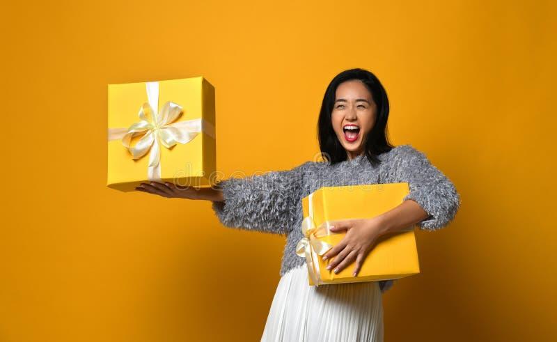 Porträt eines lächelnden hübschen Mädchens, das zwei Geschenkboxen lokalisiert über gelbem Hintergrund hält stockbilder