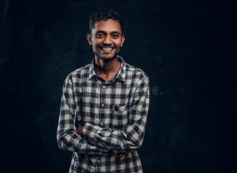 Porträt eines lächelnden indischen Kerls, der ein kariertes Hemd aufwirft mit seinen Armen gekreuzt und betrachtet die Kamera trä lizenzfreie stockfotos