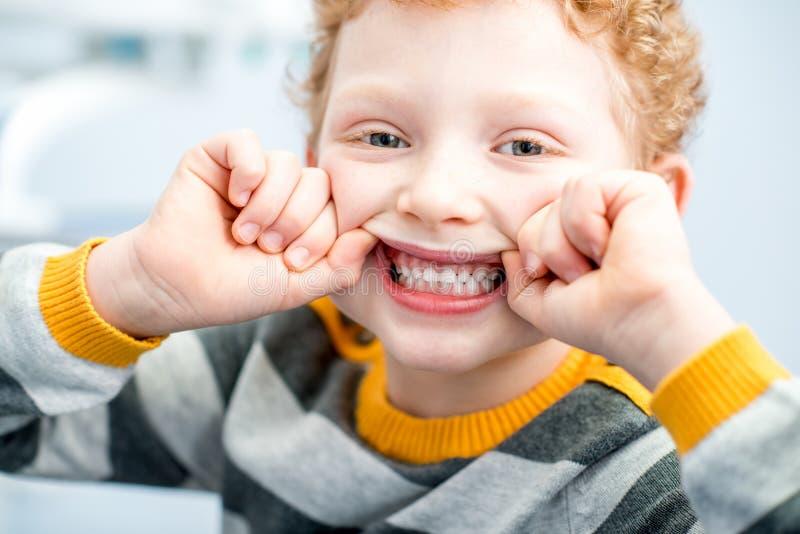 Porträt eines lächelnden Jungen im zahnmedizinischen Büro stockfotos
