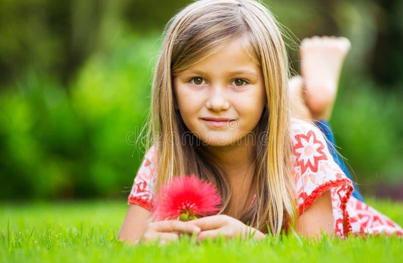 Porträt eines lächelnden kleinen Mädchens, das auf grünem Gras liegt stockfotografie