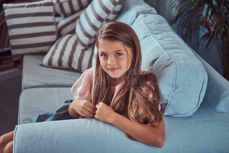 Porträt eines lächelnden kleinen Mädchens mit dem langen braunen Haar und Durchdringen blickt flüchtig und zu Hause liegt auf ein stockbild