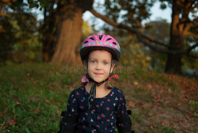 Porträt eines lächelnden kleinen Mädchens - Rollenschlittschuhläufer in einem Sturzhelm und in den Ellbogenschutzen lizenzfreie stockfotografie